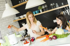 Mother and daughter in the kitchen. Mother and daughter preparing vegetables in the kitchen royalty free stock photo