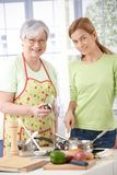 Mother and daughter in kitchen smiling Stock Image