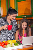 Mother and daughter in the kitchen using the laptop. royalty free stock photo