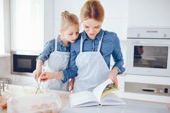 Mother with daughter in the kitchen. A young and beautiful mother in a blue shirt and apron is preparing dinner at home in the kitchen, along with her little stock images