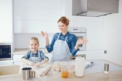 Mother with daughter in the kitchen. A young and beautiful mother in a blue shirt and apron is preparing dinner at home in the kitchen, along with her little stock photos