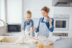 Mother with daughter in the kitchen. A young and beautiful mother in a blue shirt and apron is preparing dinner at home in the kitchen, along with her little stock photography