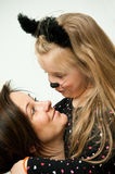 Mother with daughter in kitten costume Stock Photography