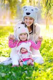 Mother and daughter in knitted hats Bears, with a doll Royalty Free Stock Image
