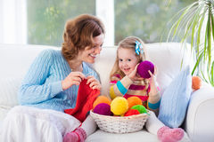 Mother and daughter knitting woolen scarf stock photography