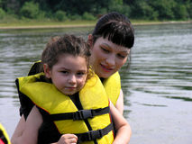 Mother and daughter by lake. Young girl in personal floatation device by lake with mother Royalty Free Stock Images