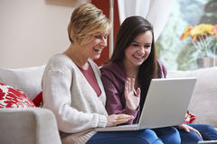 Mother and daughter on laptop. Mother and daughter smiling at laptop while using webcam royalty free stock image