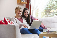 Mother and daughter on laptop. Mother and daughter enjoying surfing on the net while relaxing at home with coffee royalty free stock images
