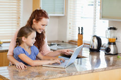 Mother and daughter with laptop behind the kitchen counter Royalty Free Stock Image
