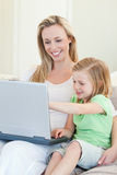 Mother and daughter with laptop on couch Royalty Free Stock Image