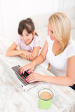 Mother and Daughter with a Laptop at home Stock Images