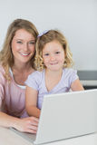 Mother and daughter with laptop at kitchen table Royalty Free Stock Photos