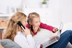 Mother And Daughter With Laptop And Phone Royalty Free Stock Photos