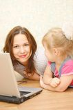 Mother and daughter with laptop on wooden  floor Royalty Free Stock Photos