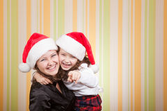 Mother and daughter laugh. Beautiful young mother and little daughter pointing finger in camera and laugh Royalty Free Stock Photography