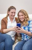 Mother and daughter laughing when looking at phone Royalty Free Stock Photos