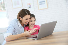 Mother and daughter laughing while playing games on the laptop Royalty Free Stock Image