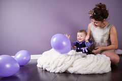 Mother and daughter are laughing together while playing with baloons Royalty Free Stock Photo