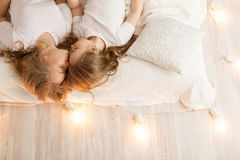 Mother and daughter lay on the bed and kiss. View from above. Togetherness. Loft interior Stock Photo