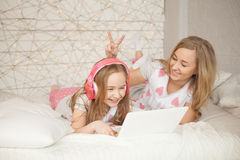 Mother and daughter lay on bed in pajamas and have fun, use laptop and listen music by pink headphones. Lifestyle. Happy Royalty Free Stock Photography
