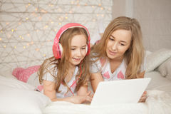 Mother and daughter lay on bed in pajamas teach and have fun, use laptop and listen music by pink headphones. Lifestyle Royalty Free Stock Photos