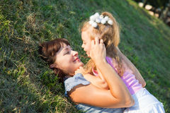 Mother and daughter lay on the grass. Mother and little daughter lay on the grass Stock Photography