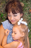 Mother and daughter lay on the grass. Mother and little daughter lay on the grass Royalty Free Stock Images