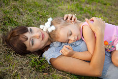 Mother and daughter lay on the grass. Mother and little daughter lay on the grass Royalty Free Stock Image