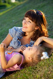Mother and daughter lay on the grass Stock Photo
