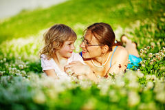 Mother and daughter laying in a grass Royalty Free Stock Photos