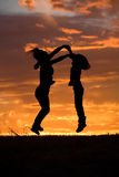 Mother and daughter leap at sunset. Stock Photography