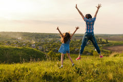 Mother and daughter leap at sunset Stock Images