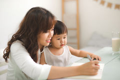 Mother and daughter are learning to write. Mother and daughter are learning to write Royalty Free Stock Image