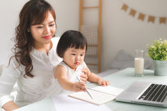 Mother and daughter are learning to write. Mother and daughter are learning to write Stock Photos
