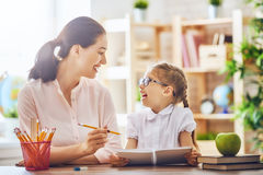Mother and daughter are learning to write. Happy family. Mother and daughter are learning to write. Adult women teaches child the alphabet Royalty Free Stock Images