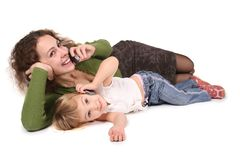 Mother and daughter lie. They talk on the cell phones on the the white stock photo