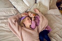 Mother and daughter lie on the big bed. And fooling around in sweaters and jeans royalty free stock images