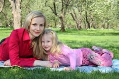 Mother with daughter lie on grass royalty free stock photo