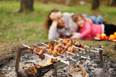 Mother and daughter lie near campfire with grill Stock Photo