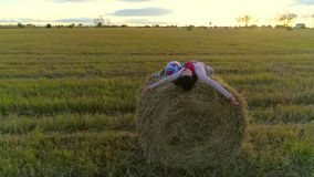 Mother with daughter lie on the straw stack on the rustic field in the sunset. A mother with a little daughter lie on the straw stack on the rustic field at the stock video