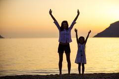 Mother and daughter lifting arms while standing on the beach Stock Photography