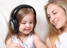 Mother and daughter listen to the music Stock Photos