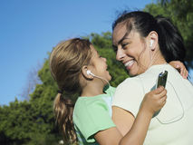 Mother and daughter (6-8) listening to MP3 player, sharing headphones, smiling, close-up (tilt) Royalty Free Stock Image