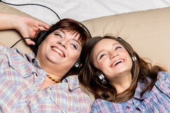 Mother and daughter listening to music in bed. Royalty Free Stock Photos