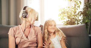 Mother and Daughter Listening to Music. Joyful attractive mother and pretty preteen daughter having fun and listening to music. spending free time together stock footage