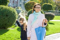 Mother and daughter little girl an elementary school student holding hands go to school. Autumn city background.  Royalty Free Stock Photos