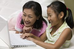 Mother and Daughter in living room Using Laptop Together Stock Photo