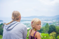 Mother and daughter look around from mountain view point on trop Stock Image