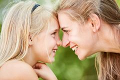Mother and daughter look each other in the eye. Happy mother and daughter look deep into each other`s eyes in the green royalty free stock photos