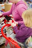 Mother and daughter look gloves in supermarket. Stock Images